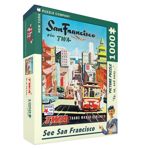 "This box contains a 1000 piece jigsaw puzzle. On the front is the image of a completed puzzle, which pictures a tour guide gesturing to a busy street in San Francisco with an airplane flying over. At the top of the image are the words, ""San Francisco via TWA"" in black and green lettering."