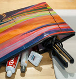 "The ""Sunset Highway"" Jumbo Pouch is filled with toothpaste, dental floss, and and pens"