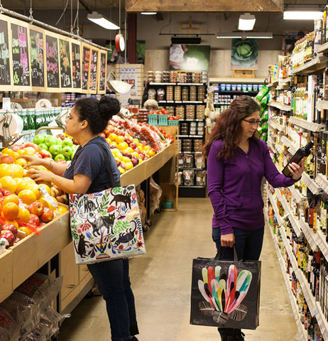 Pictured is two ladies in the produce department of a grocery store using there shopper bags.