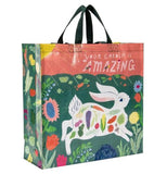 "The ""Your Garden is Amazing"" Shopper Bag has a pink banner on top that says ""Your Garden is Amazing"" above a white bunny running through a flower garden with vegetables on its body."