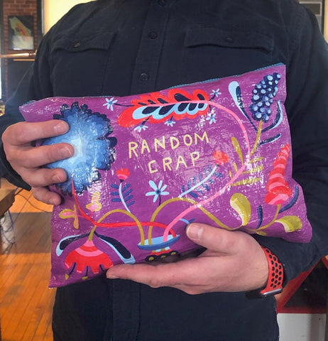 "A person's hands are shown holding the ""Random Crap"" zip-up pouch."