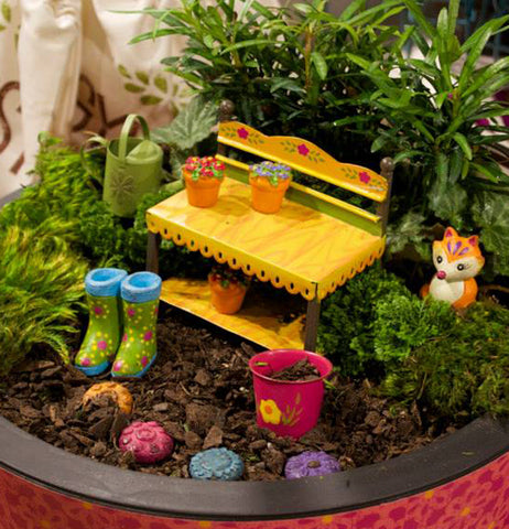 A close up of potted mini garden with green plants, a yellow bench, a fox, green garden boots, a green watering can and a pink bucket.