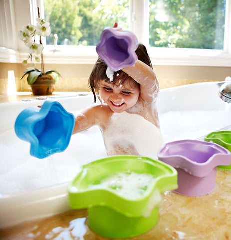 A little girl is shown playing with the star-shaped stacking cups in the bath tub.