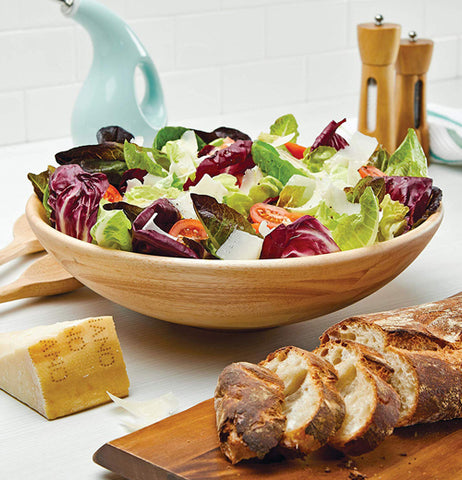"The ""Parawood"" Salad Bowl is being used on the table for salads during dinnertime."