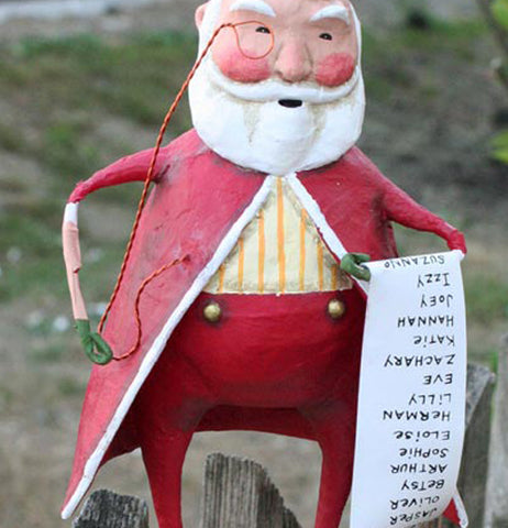 The Santa Claus figurine with the monocle and Christmas list is shown standing with a green hill behind him.