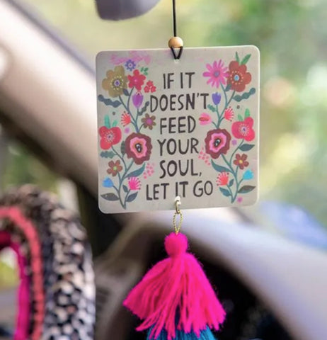 """Let It Go"" square air freshener with flower design hanging from a car rear view mirror with pink and blue tassels hanging down from it."