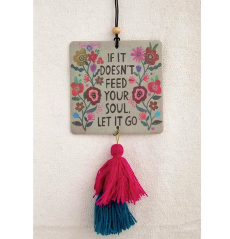 """Let It Go"" square air freshener wth flower design and black words with pink and blue tassels hanging down on a white background."