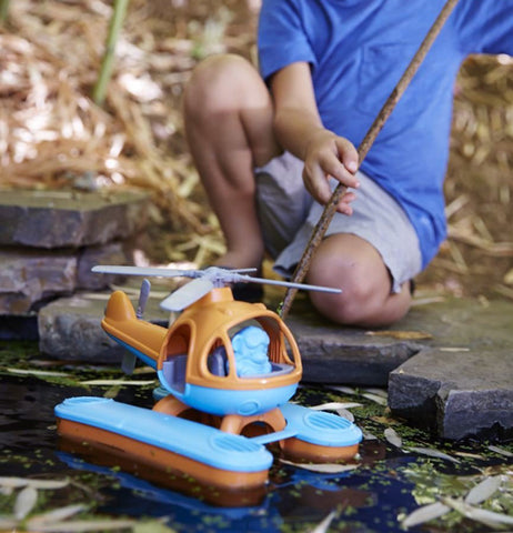 A little boy playing with his helicopter in a pond.