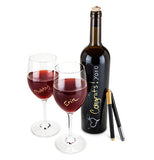 The metallic bottle pens are leaning on a bottle of wine with two glasses of wine and the pens have written on the bottle and glasses.
