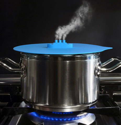 A light blue lid with a freight ship like outlet with steam coming from the top sitting on a steaming pot on the stove.