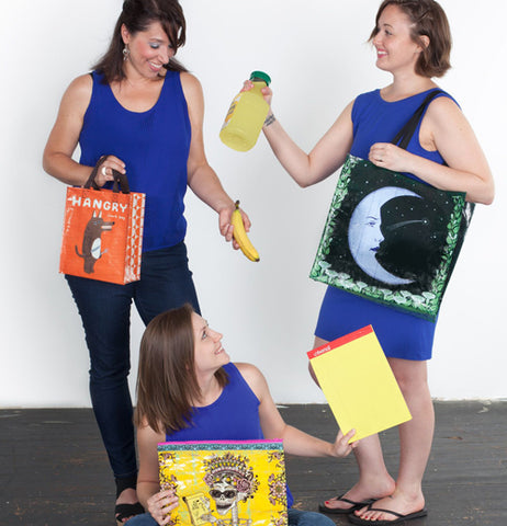 Three women all wearing blue outfits showing off what they are carrying in their bags, one has a small orange bag with a bear, another has a black bag with a part moon with a face, the third has a zipper bag with a sugar skull.