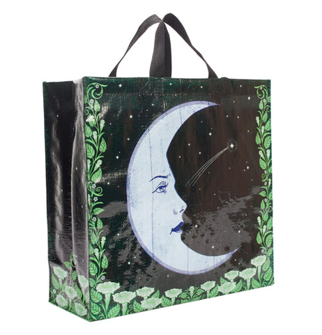 a black bag with a sideways view of the moon with a face and soft green colored foliage around the bottom of the bag and going up the front and back side edges