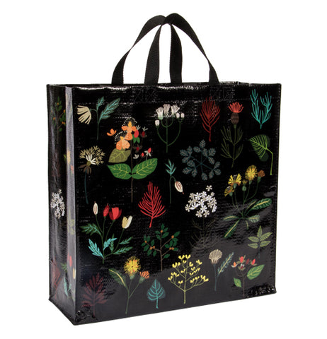 This black bag has an assortment of different plant illustrations covering its top. The plants include green, red, and blue leaves. A few orange flowers cover the top, and some green and yellow bushes cover the bottom.
