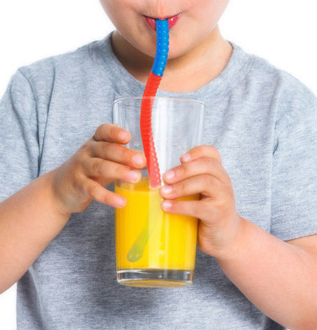 Child drinking a glass of orange juice while using a Slinky drinking straw