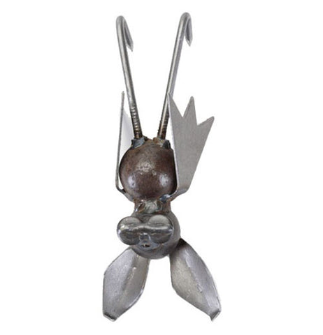 This metal sculpture is of a small bat with large ears and folded wings hanging from its feet.