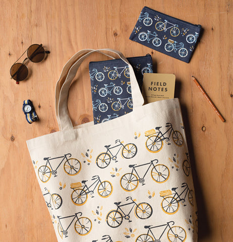 The two black bags with the bicycle designs are shown mixed with a white bag with a bicycle design lying on a wooden table.
