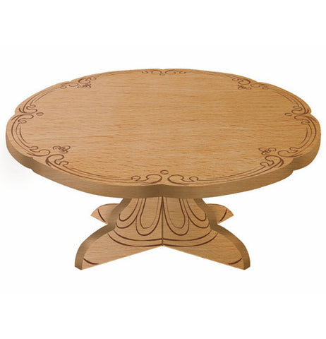 A beechwood cake pedestal with etched designs around the edge and the base.