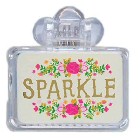 Clear plastic toothbrush cover with a white label featuring a yellow, green, pink flower design with gold letters that say Sparkle on the front.