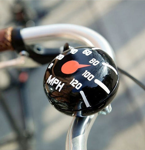 The black and white bike bell is shown tied to a bike handlebar.