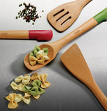 This picture shows a red- and a green-tipped Switchit dual-ended iwooden spoon with pasta on the green one and next to it. It also featuresa slotted wooden spoon with a silicone scraper on the othersome seeds next to it.