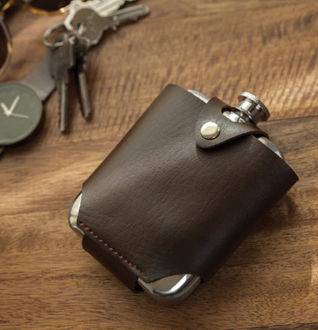 The flask and traveling case sits on the wooden table with the keys.