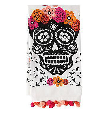 This festive sugar skull tea towel is black with white outline and has pretty orange and pink flowers on its head and below it with vines all around it. Shown folded.