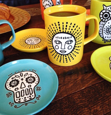 The Cuppa Color Yellow Sun coaster sits on the table with other saucers and cups.