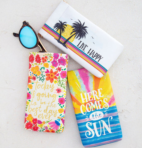 "The ""Here Comes the Sun"" sunglass case is shown lying between two other sunglass cases with floral and tropical beach designs."