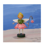The sweet pea fairy is standing on sand close to the ocean.