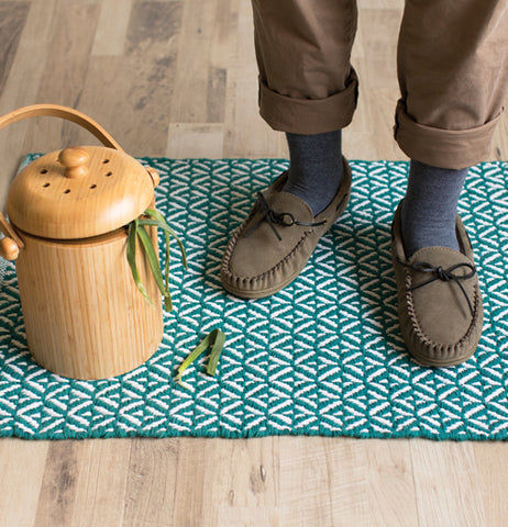 A man's slippers are shown standing on the blue weave carpet.