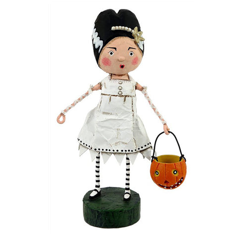 This figurine is of a woman wearing a bride of Frankenstein costume with a white ragged dress and is carrying a pumpkin shaped pail.