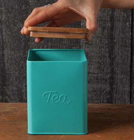 A hand is opening the lid of a Tea tin canister.
