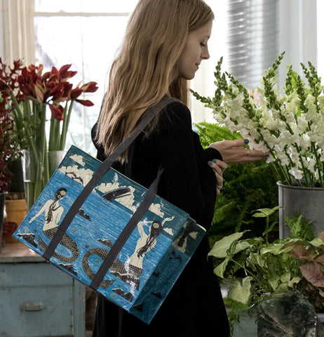 The blue mermaid tote bag is shown slung around a woman's shoulder.