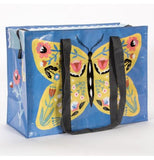 "The ""Butterfly"" Shoulder Tote Bag features a design of a yellow butterfly with colorful floral designs on it's wings over a blue background."