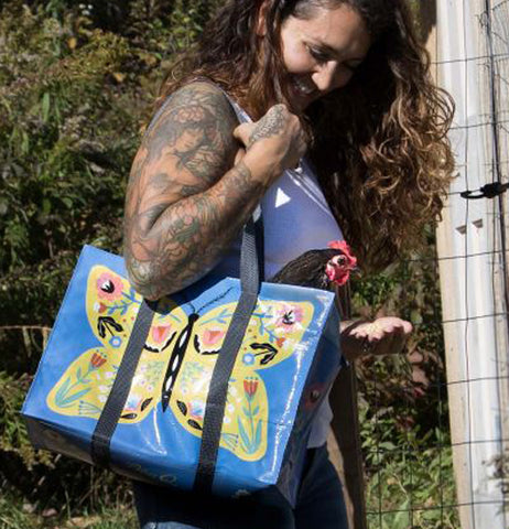 "A lady with a full sleeve tattoo is carrying the ""Butterfly"" Shoulder Tote Bag."