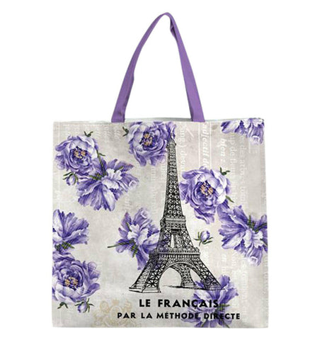 "The Small ""French Kiss"" Tote Bag features black text reading ""Le Francais Par La Methode Directe"" along with the Eiffel Tower with purple flowers over a light peach background."