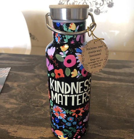 "The ""Kindness Matters"" bottle is shown sitting on a wooden table with its lid and price tag attached."