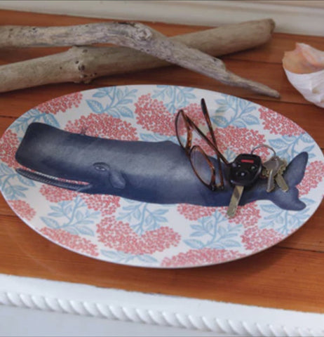 A pair of glasses and some car keys are shown lying on top of the whale designed plate.