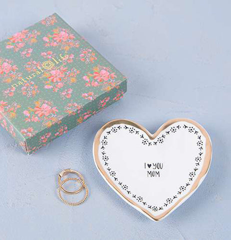 Heart shaped trinket dish with black pattern over a white background and gold foil edge. It reads I heart mom with heart symbol instead of word. It is placed next to a green box with pink flowers and a set of engagement rings.