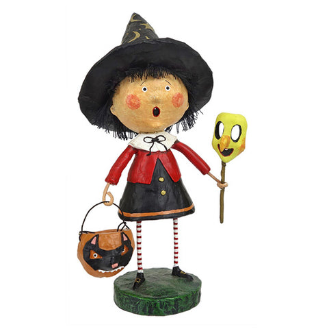 A little witch carrying a treat bucket and holding a mask