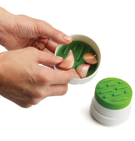 Garlic Peeler with green inside showing. It has garlic placed inside for peeling.