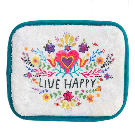 "This white sink matt with teal edges has a design of yellow, red, and purple flowers with a red heart in the center. Below the heart are the words, ""Live Happy"" in black lettering."