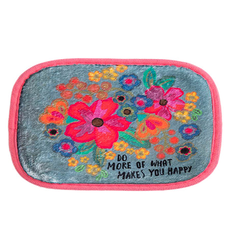 "This blue sink matt with red edges has a floral design of hot pink, orange, blue, and yellow flowers. At the bottom below the flowers are the words, ""Do More Of What Makes You Happy"" in black lettering."