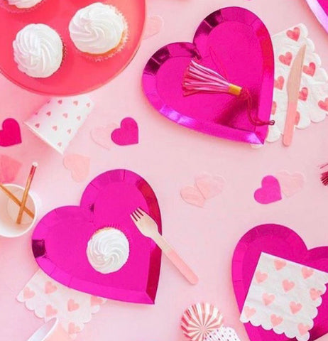 Three pink heart-shaped plates are shown with a tassel, a fork, and a white and pink napkin on them.