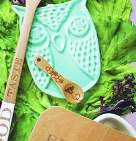 The beechwood spoon is resting on a teal, owl shaped trivet.