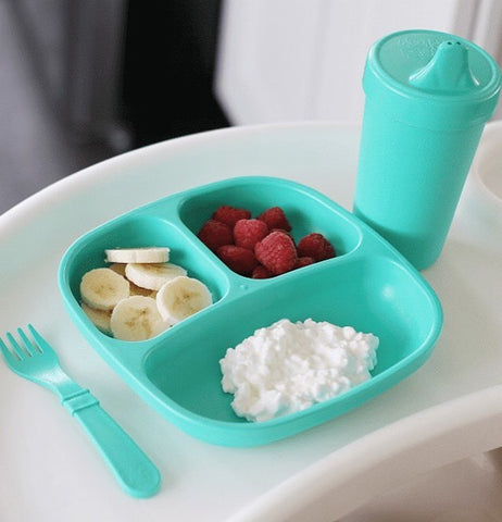 "The ""Aqua"" Spill Proof Cups sits on a white high chair tray with a matching divided plate and fork."