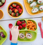 A child's hand picks up strawberry from a place setting featuring a green divided plate and flanked by a red fork and spoon from the utensil set.