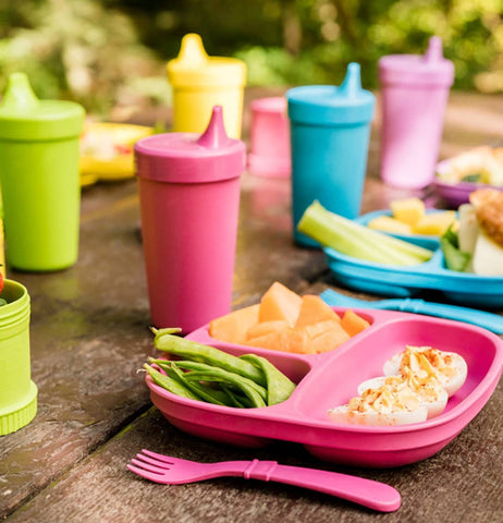 "The ""Butterfly"" Spill Proof Cups sits on the table with a matching divider plate with deviled eggs, snap peas, cut cantaloupe pieces and utensils."