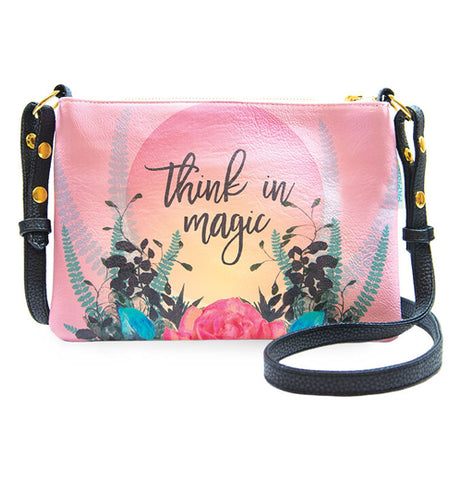 Pink hand bag with floral design that says Think in Magic. It has a black adjustable strap.