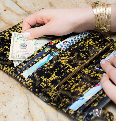 "Money and cards are filled in the ""Black Gilded Flowers"" wallet with her hands."
